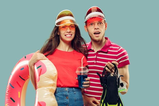 Het portret van de halve lengte van het mooie jonge paar geïsoleerd. glimlachende vrouw en man in kappen en zonnebril met zwemuitrusting. gelaatsuitdrukking, zomer, weekendconcept. Gratis Foto