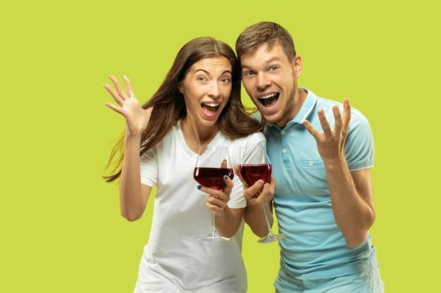 Het portret van de halve lengte van het mooie jonge paar geïsoleerd. vrouw en man met glazen rode wijn selfie maken. gelaatsuitdrukking, zomer, weekendconcept. trendy kleuren. Gratis Foto