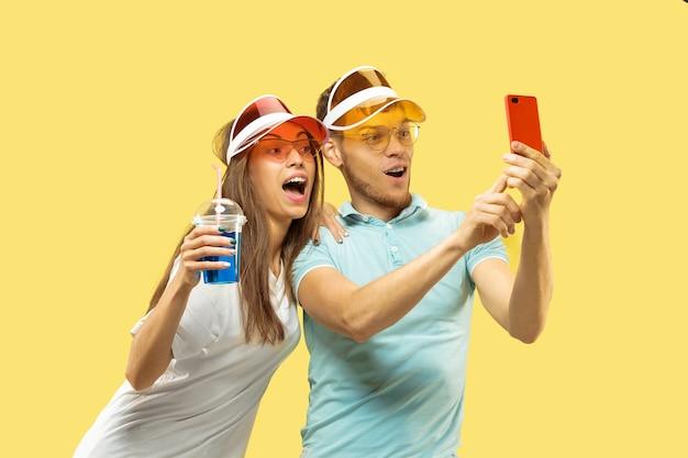 Het portret van de halve lengte van het mooie jonge paar geïsoleerd. vrouw en man permanent met drankjes selfie maken. gelaatsuitdrukking, zomer, weekendconcept. trendy kleuren. Gratis Foto