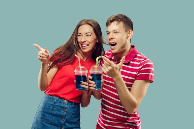 Het portret van de halve lengte van het mooie jonge paar geïsoleerd. vrouw en man staan met drankjes glimlachend en omhoog. gelaatsuitdrukking, zomer, weekendconcept. trendy kleuren. Gratis Foto