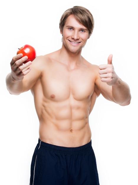 Het portret van de jonge gelukkige appel van de bodybuilderholding in zijn hand en toont duimen omhoog teken - dat op witte muur wordt geïsoleerd. Gratis Foto