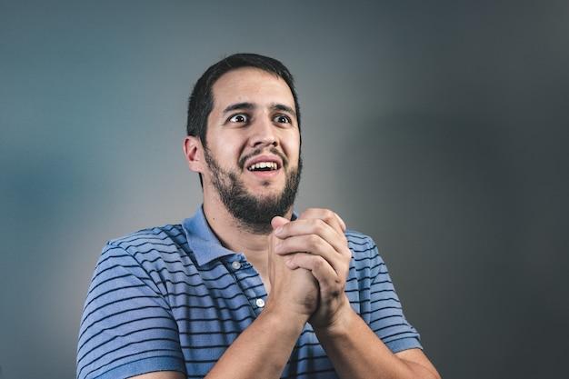 Het portret van de mens die clasped handen, vragend om hulp of verontschuldiging toont. vergeef me alsjeblieft het concept Premium Foto
