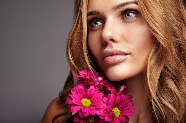 Het portret van de schoonheidsmanier van jong blond vrouwenmodel met natuurlijke make-up en perfecte huid met het heldere ñrimson-chrysantenbloem stellen Gratis Foto