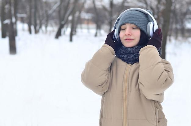 Het portret van de winter van jong meisje met hoofdtelefoons Premium Foto