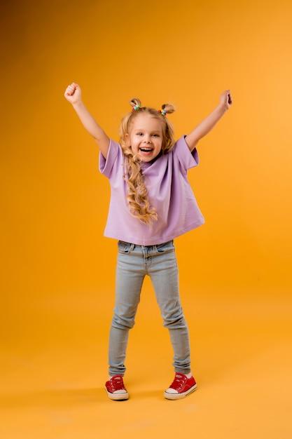 Het portret van een gelukkig kindmeisje isoleert op een gele ruimte, ruimte voor tekst Premium Foto