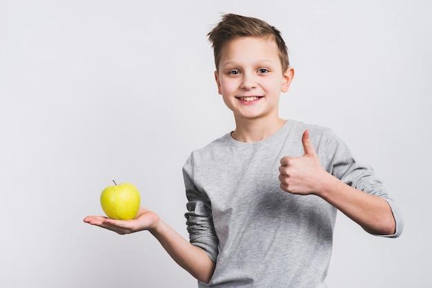 Het portret van een glimlachende jongen die groene appel op hand houdt die duim toont ondertekent omhoog Gratis Foto