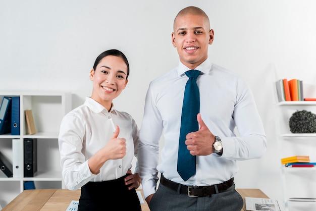 Het portret van een jonge glimlachende zakenman en een onderneemster die duim tonen ondertekenen omhoog Gratis Foto
