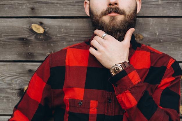 Het portret van een jonge modieuze gebaarde mens kleedde zich omhoog in jeans en een ware arbeiderszwarte door rood overhemd. Premium Foto