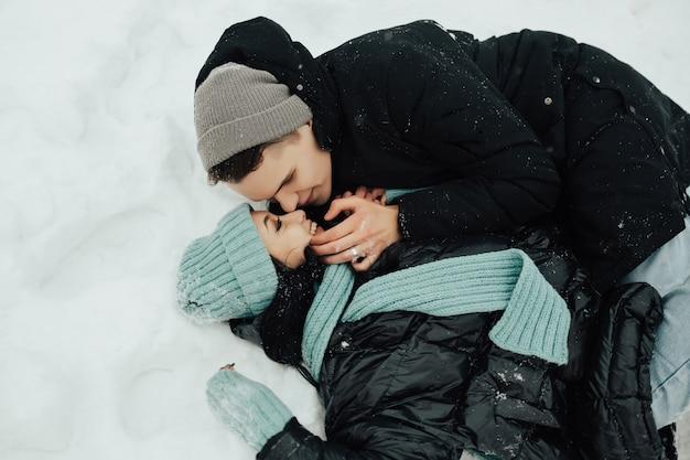 Het portret van een liefdevol paar ligt in de sneeuw in de winter in het bos. Premium Foto