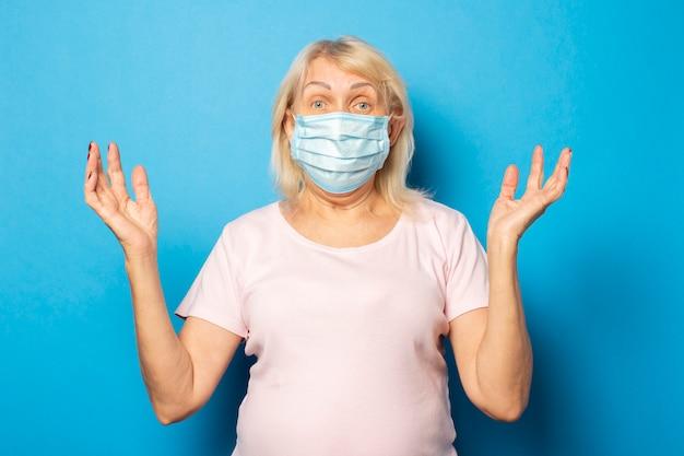Het portret van een oude vriendschappelijke vrouw in een t-shirt en een medisch beschermend masker haalt handen op blauwe muur op. emotioneel gezicht. conceptvirus, quarantaine, vuile lucht, pandemie. gebaar van angst, zorgen Premium Foto