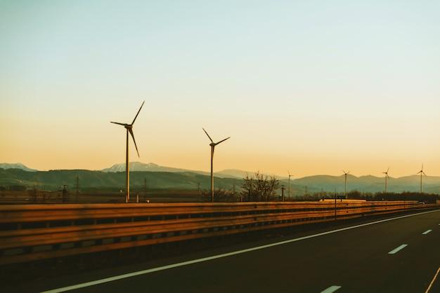 Het portret van eolian-energie, gaat groen, windturbines langs de weg bij zonsondergang Premium Foto