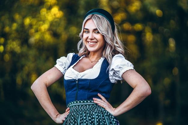 Het portret van gelukkig vrij blond meisje in dirndl, de traditionele kleding van het bierfestival, die zich in openlucht met blured kleurrijke bomen erachter bevinden Premium Foto