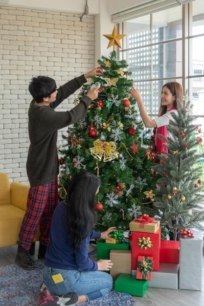 Het portret van gelukkige jonge aziatische dame verfraait kerstboom met haar vrienden, kerstmistijd, vakantie Premium Foto