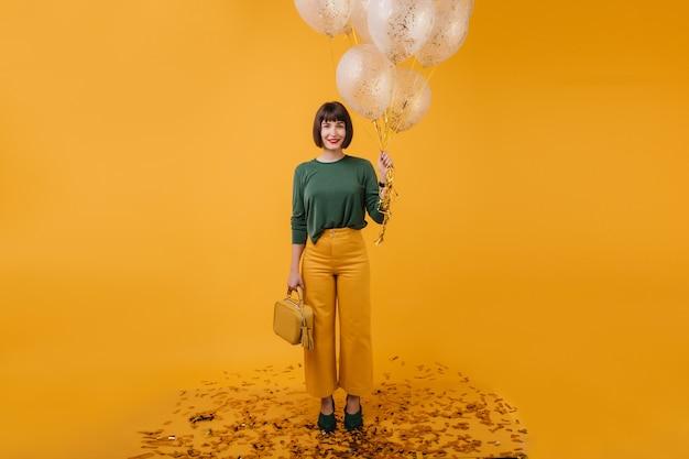 Het portret van gemiddelde lengte van mooie geïsoleerde vrouw met beurs. binnen schot van stijlvolle feestvarken bos van partij ballonnen te houden. Gratis Foto