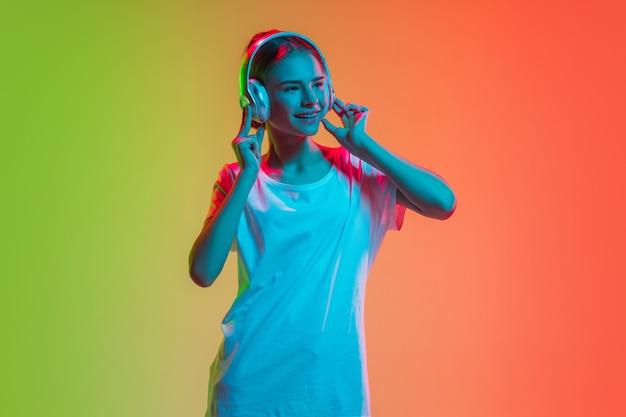Het portret van het jonge kaukasische meisje op gradiënt groen-oranje in neonlicht Gratis Foto