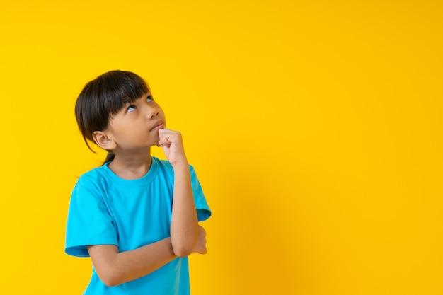 Het portret van het jonge meisje denken en krijgt idee, thais studentenjong geitje in zachte blauwe overhemds status en gissing geïsoleerd Premium Foto