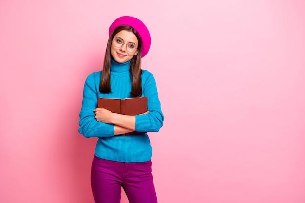Het portret van het mooie mooie meisje van de boekminnaar omhelst haar favoriete leerboek van de verhaalpoëzie draagt blauwpaarse knappe kleren. Premium Foto