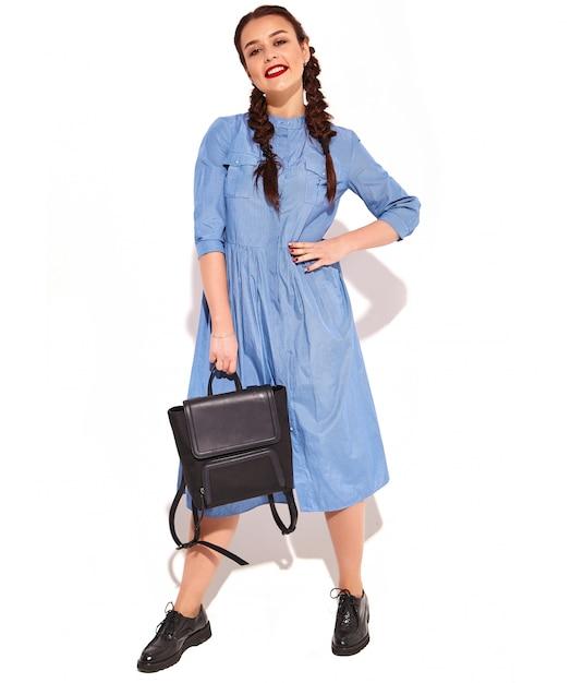 Het portret van jong gelukkig het glimlachen vrouwenmodel met heldere make-up en rode lippen met twee vlechten dient binnen geïsoleerde de zomer kleurrijke blauwe kleding en rugzak in. Gratis Foto