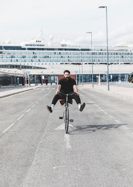 Het portret van jonge personenvervoerfiets op weg met benen schopte uit voor cruise Gratis Foto