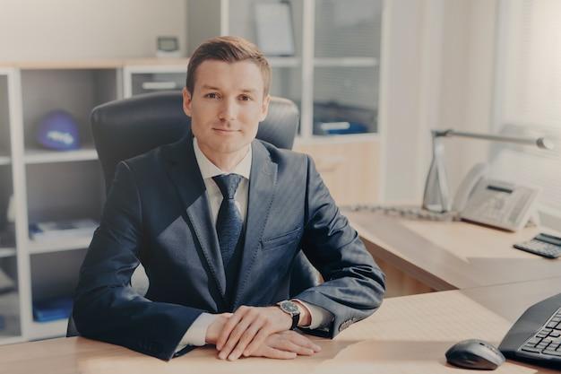 Het portret van knappe welvarende mannelijke manager zit bij kabinet, kijkt direct in camera Premium Foto