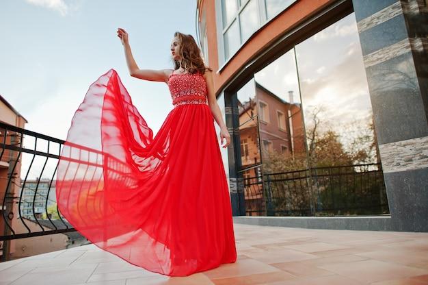 Het portret van modieus meisje bij rode avondjurk stelde achtergrondspiegelvenster van de moderne bouw bij terrasbalkon. blazende jurk in de lucht Premium Foto