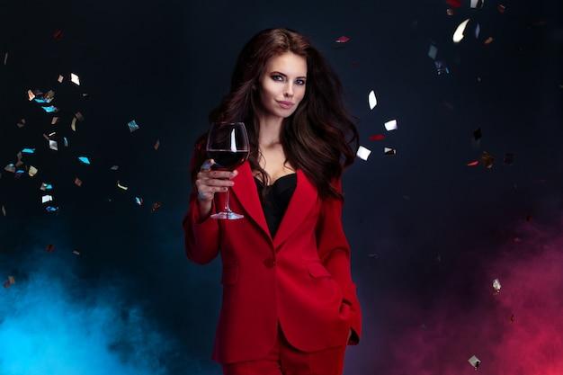 Het portret van mooie vrouw in rood kostuum houdt wijnglas terwijl status onder dalende heldere confettien Premium Foto