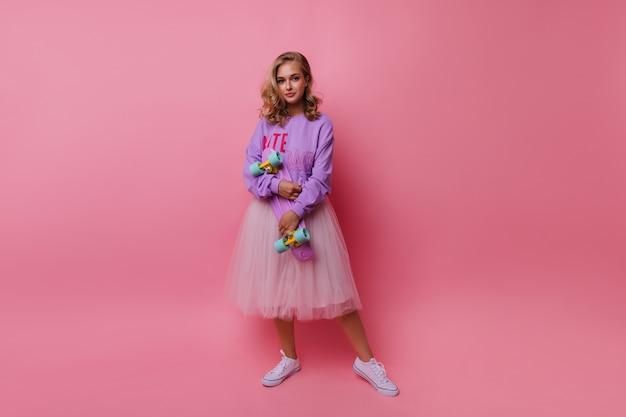 Het portret van volledige lengte van een enthousiaste jongedame draagt een weelderige witte rok. romantisch meisje met skateboard staande op rooskleurig. Gratis Foto