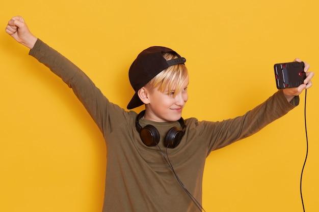 Het portret van weinig jongen die zijn moderne cellphone houdt en video bekijkt, gebruikend draadloos internet en hoofdtelefoons, verheugt zich met omhoog handen Gratis Foto