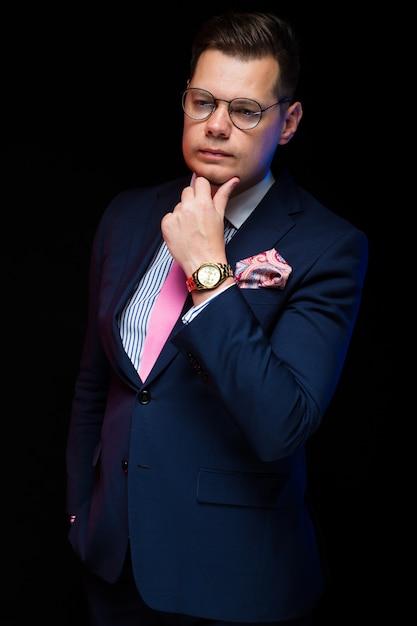 Het portret van zekere knappe zakenman die zijn hand houden dichtbij baard op zwarte achtergrond met dient zak in Premium Foto
