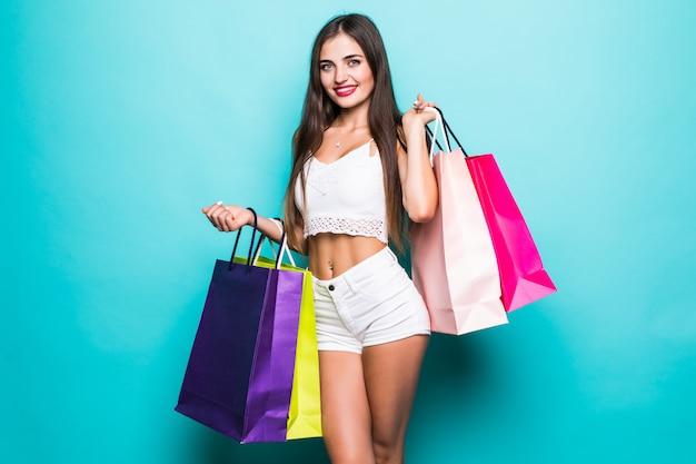 Het positieve vrouwengreep doet winkelen geïsoleerd over muur van de wintertalings de turkooise kleur in zakken Gratis Foto