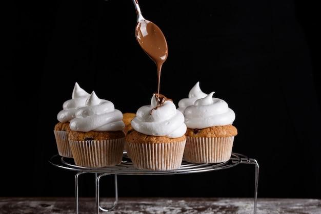 Het proces van het maken van cupcakes, het coaten van een crème uit een spuitzak in de handen van een banketbakker. Premium Foto