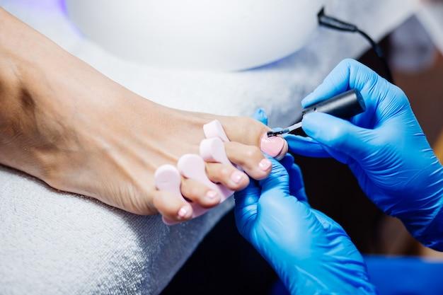 Het proces van professionele pedicure met meester in blauwe handschoenen die lichtroze gelpoets toepassen Gratis Foto