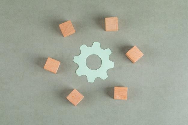 Het reparatieconcept met houten kubussen, montagesymbool op grijze lijstvlakte lag. Gratis Foto