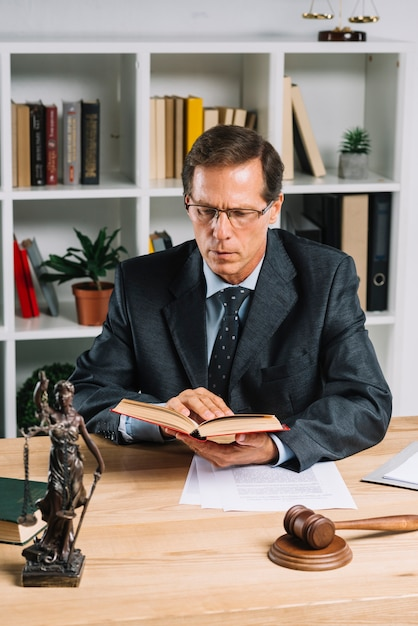 Het rijpe mannelijke boek van de advocaatlezing met hamer en rechtvaardigheidsstandbeeld op houten lijst Gratis Foto