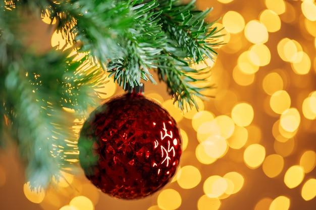 Het rode kerstmisbal hangen op sparrentak over gouden bokehlichten als achtergrond Premium Foto