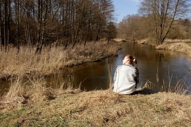 Het roodharige gembermeisje kleedde zich in jeans en grijze hoodiezitting op gras op de bank van bosrivier en ver weg kijkend Premium Foto
