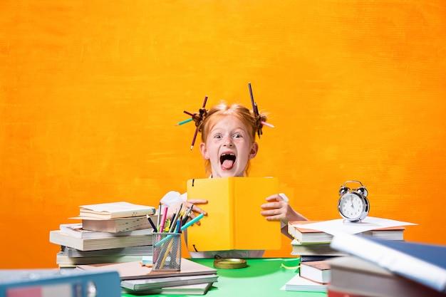 Het roodharige tienermeisje met veel boeken thuis. studio-opname Gratis Foto