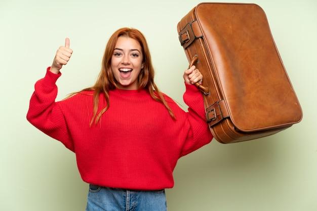 Het roodharigemeisje van de tiener met sweater die een uitstekende aktentas houdt Premium Foto
