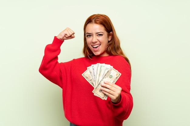 Het roodharigemeisje van de tiener met sweater over geïsoleerde groene achtergrond die heel wat geld neemt Premium Foto