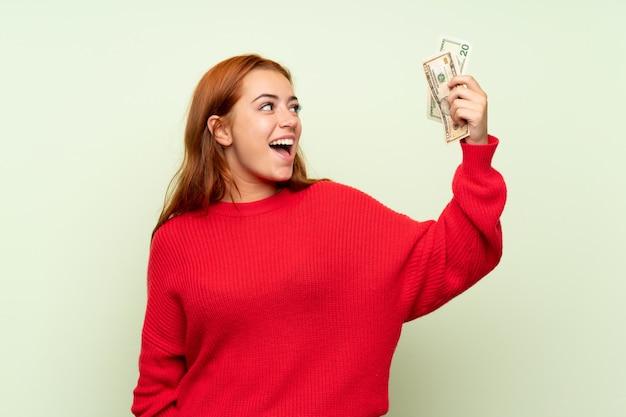 Het roodharigemeisje van de tiener met sweater over geïsoleerde groene muur die heel wat geld neemt Premium Foto
