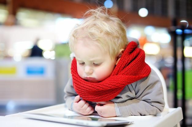 Het schattige de jongen van de blondepeuter spelen binnen met een digitale tablet Premium Foto
