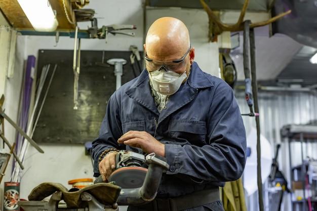 Het scherpe staal van de zware industriearbeider met hoekmolen bij de autodienst Premium Foto