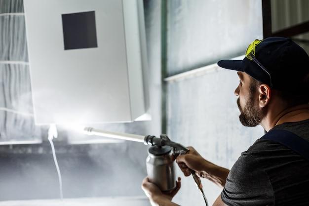 Het schilderen van de arbeider detail met het pistool van de luchtnevel. Gratis Foto