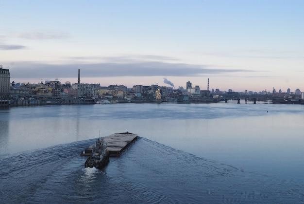 Het schip drijvend in de rivier de dnjepr. kiev stadslandschap op de achtergrond. 2018/11/17 Premium Foto