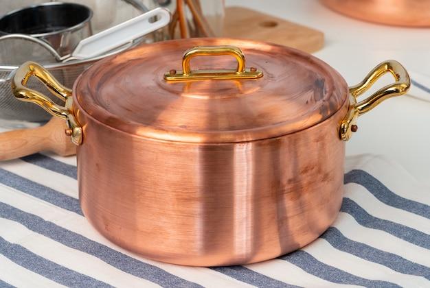 Het schone kookgerei, werktuigen sluit omhoog op lijst in moderne keuken Premium Foto
