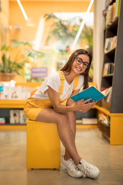 Het schoolmeisjezitting van de tiener met boek op bank Gratis Foto