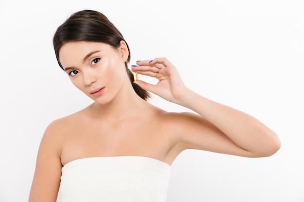 Het schoonheidsportret van gezonde aziatische vrouw met donkere capsule van de haarholding meds of vitamine in haar hand, die over wit stellen Premium Foto