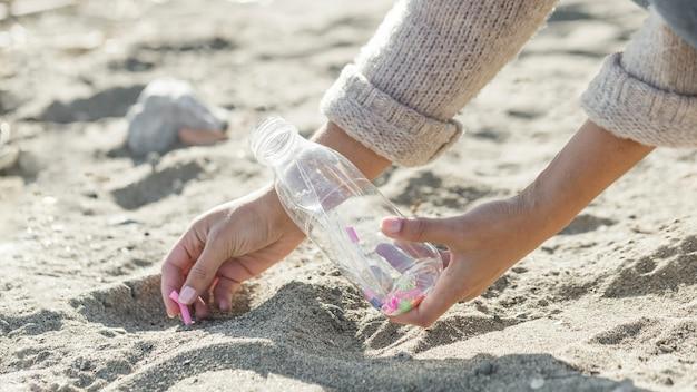 Het schoonmakende zand van de close-upvrouw van fles Gratis Foto