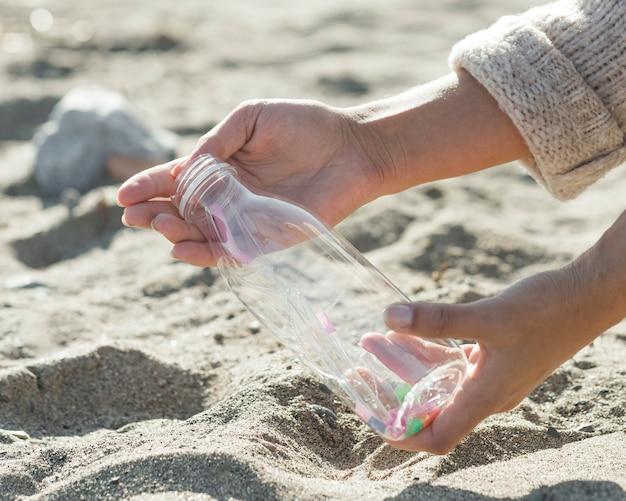 Het schoonmakende zand van de close-upvrouw van plastic fles Gratis Foto
