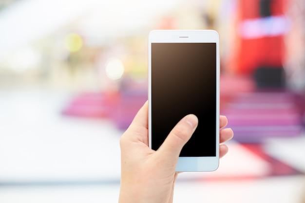 Het schot van de vrouwelijke hand van `s houdt slimme telefoon met het lege exemplaarscherm voor uw reclamecontent of promotietekst Gratis Foto